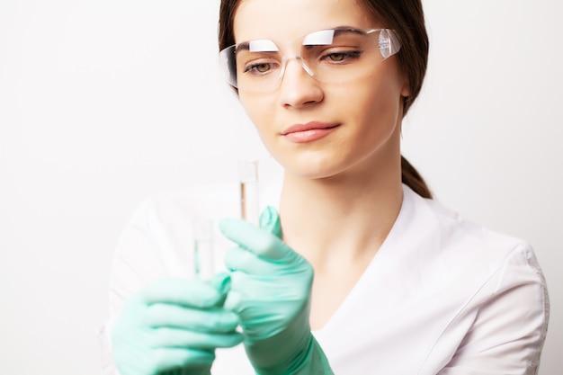Médico na clínica segurando tubos de ensaio com vacina experimental