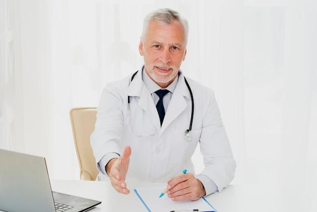 Médico na mesa segurando a mão dele