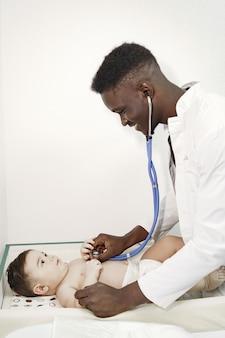 Médico negro. bebê na fralda. africano com estetoscópio.