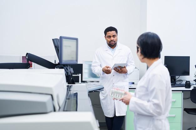 Médico negro falando com colega sobre pesquisas de laboratório
