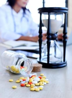 Médico no consultório com comprimidos e ampulheta