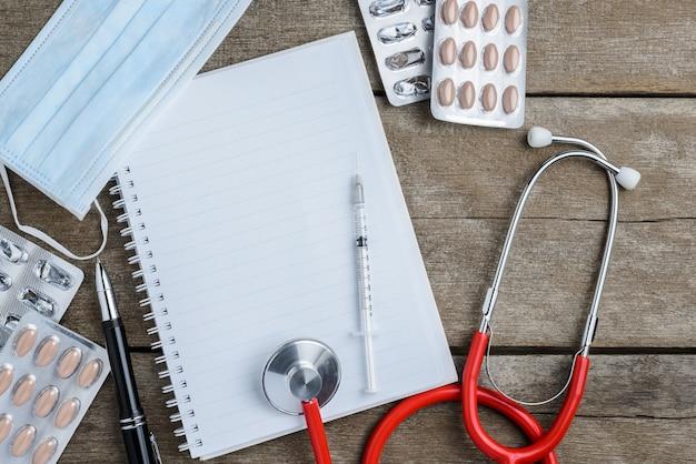 Médico no local de trabalho com um estetoscópio na mesa de madeira