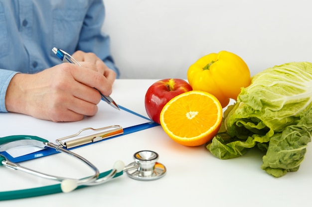 Médico nutricionista escrevendo plano de dieta na mesa