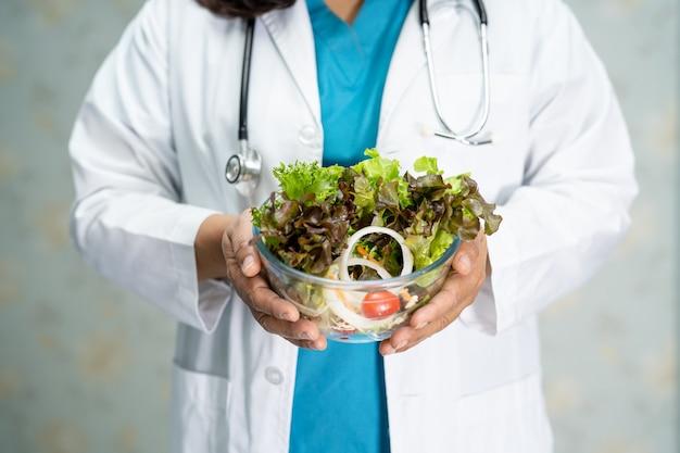 Médico nutricionista segurando comida de salada de vegetais em uma tigela de vidro.