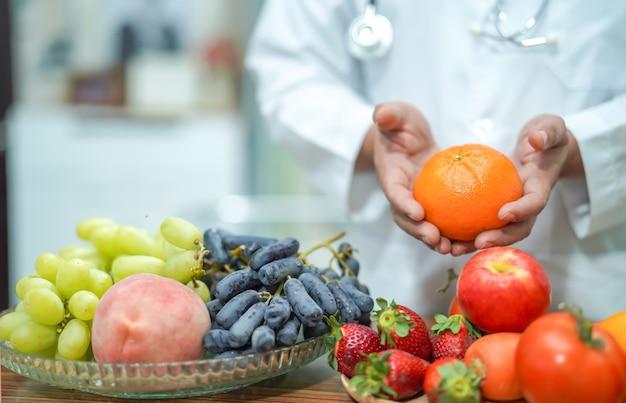 Médico nutricionista segurando laranja.