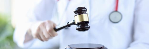 Médico oficial de jaleco branco segura o martelo de madeira para o conceito de contencioso médico de juiz