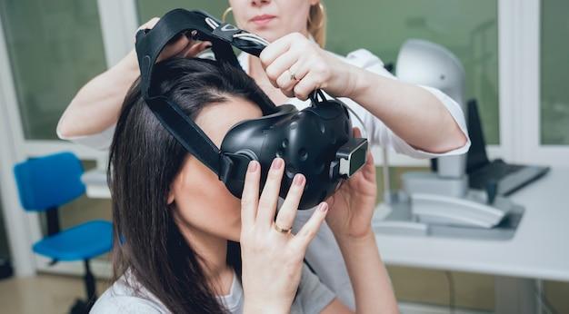 Médico oftalmologista verifica a visão da garota com a ajuda de óculos de realidade virtual.