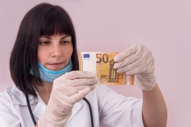 Médico olhando para uma nota de cinquenta euros segurando-a com luvas