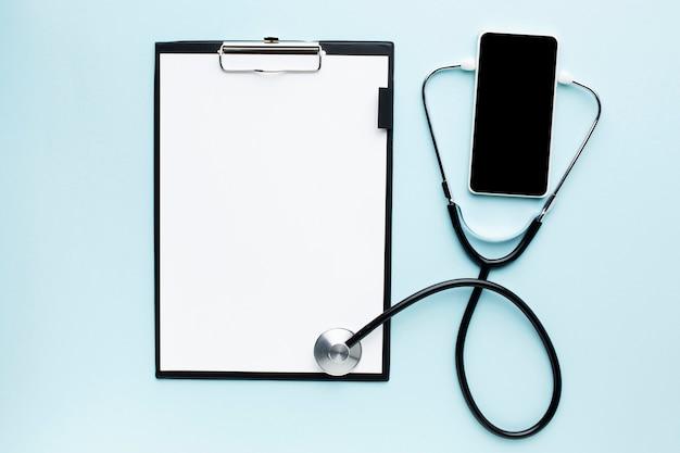 Médico on-line no telefone móvel e conceito de estetoscópio com o bloco de notas