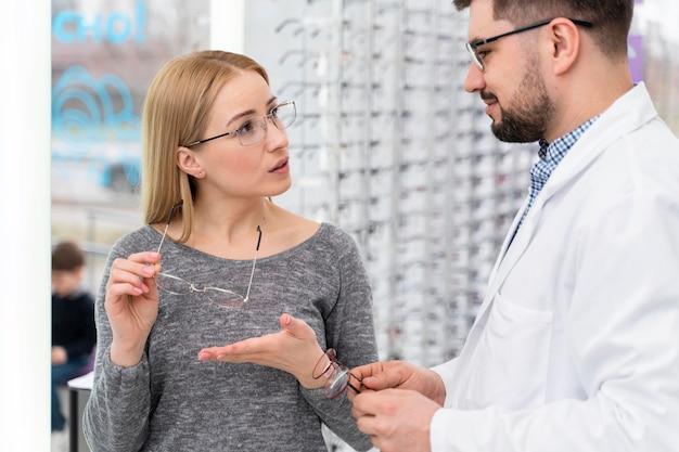 Médico óptico na loja com cliente