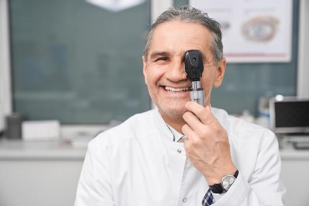 Médico optometrista sorrindo, posando, segurando o dispositivo de teste do olho.