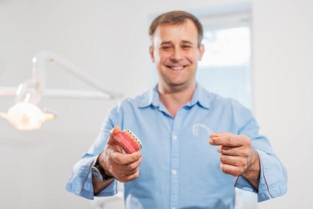 Médico ortodontista segurando alinhadores e aparelho ortodôntico mostra-os na clínica