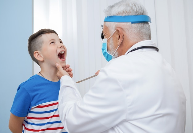 Médico otorrinolaringologista examinando a garganta do garoto.