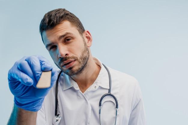 Médico otorrinolaringologista masculino europeu com espátula médica. jovem com estetoscópio vestindo jaleco branco e luvas de látex. isolado em um fundo cinza com luz turquesa. sessão de estúdio