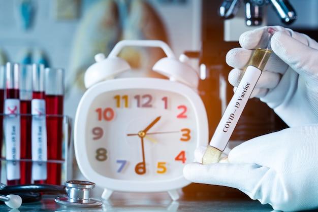 Médico ou cientista ou médico, segurando o tubo com a vacina ncov coronavirus para proteger o vírus covid-19