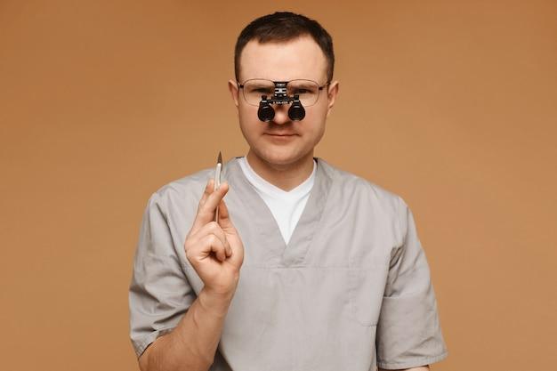 Médico ou cirurgião adulto em lupas, posando com um bisturi no fundo bege, isolado.