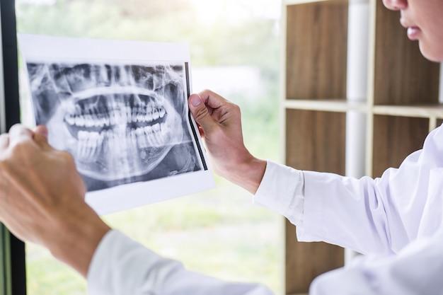 Médico ou dentista segurando e olhando para raio x dental