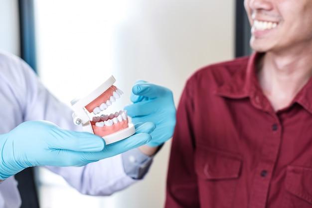 Médico ou dentista trabalhando com modelo de mandíbula e recomendar o paciente ao tratamento