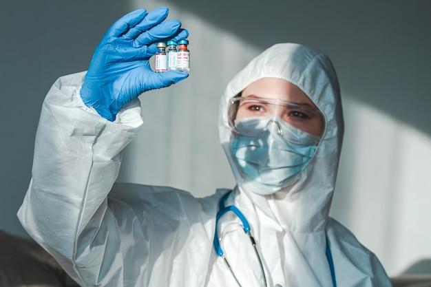 Médico ou enfermeira em uma roupa de proteção segura uma vacina covid 19 de diferentes empresas farmacêuticas em uma das mãos