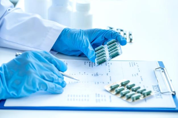 Médico ou enfermeira segurando o comprimido do remédio e prescrever no exame médico do consultório da farmácia