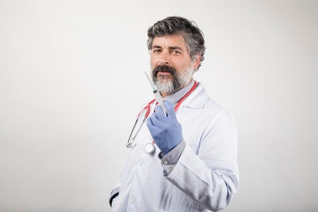 Médico ou enfermeiro em uniforme branco com seringa e luvas