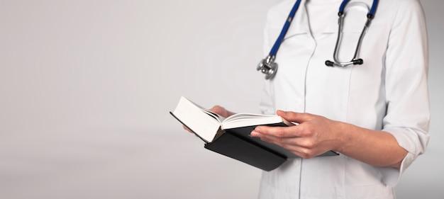Médico ou estudante de medicina em uniforme, lendo um livro grosso sobre medicina, prepare-se para o exame com o livro didático. banner com lugar para texto.