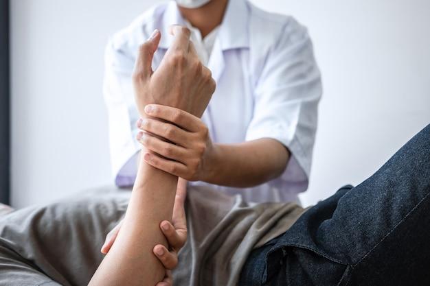 Médico ou fisioterapeuta trabalhando examinando tratamento de lesão no braço de paciente atleta do sexo masculino, alongamento e exercícios, fazendo a terapia de reabilitação da dor na clínica.