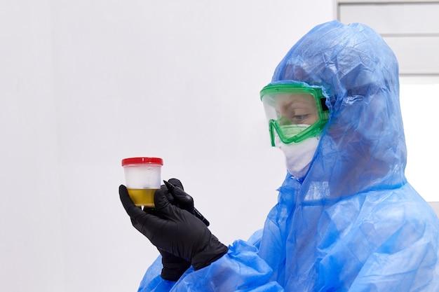 Médico ou técnico procurando amostra de urina em frasco preparado para exame de urina com microscópio