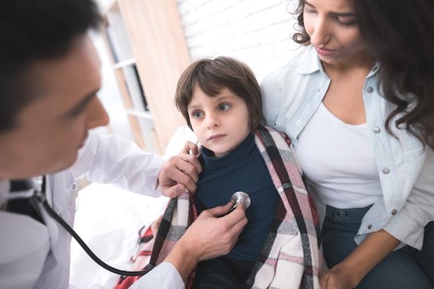 Médico ouve os pulmões de um menino doente em um estetoscópio.