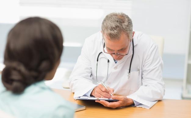Médico ouvindo seu paciente e tomando notas