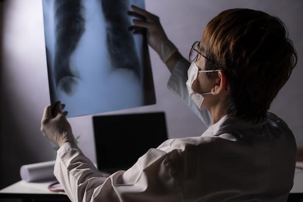 Médico parecendo preocupado ao inspecionar filme de raio-x dos pulmões durante a crise de surto de pandemia de covid-19