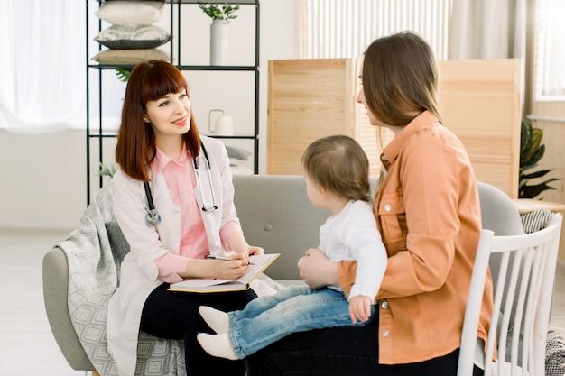 Médico pediatra amigável jovem fala com a mãe do bebê após exame