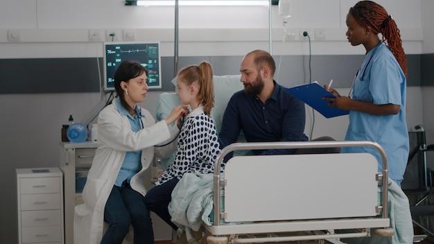Médico pediatra, consultando os pulmões, ouvindo os batimentos cardíacos, usando um estetoscópio médico