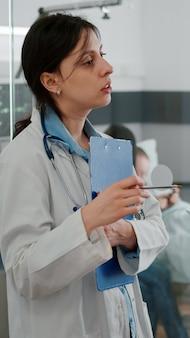 Médico pediatra discutindo sintoma de doença com enfermeira afro-americana, examinando o diagnóstico