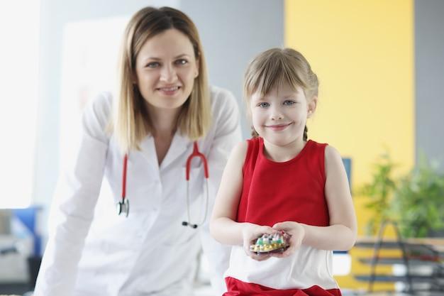 Médico pediatra e menina segurando pílulas médicas conceito de medicamentos para bebês