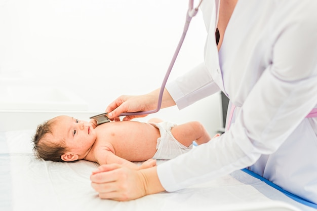 Médico pediatra examina menina com estetoscópio, verificando a batida do coração