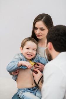 Médico pediatra examinando garoto garoto feliz. mãe segurando bebê.