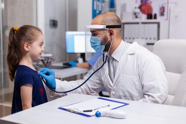 Médico pediatra examinando menina com estetoscópio para doença no consultório médico