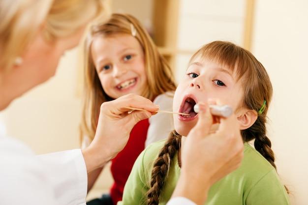 Médico pediatra examinar a garganta da menina