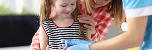 Médico pediatra faz exame de sangue de uma garotinha, close-up