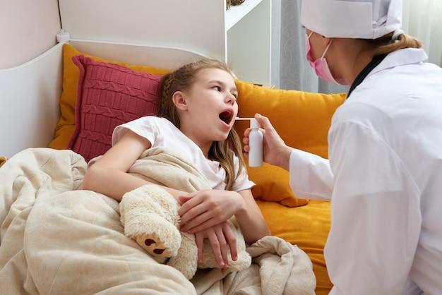 Médico pediatra usando spray médico para jovem em casa, dor de garganta