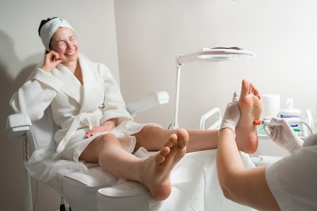Médico podólogo realiza o procedimento de tratamento de procedimentos cosméticos das pernas de uma mulher dos pés