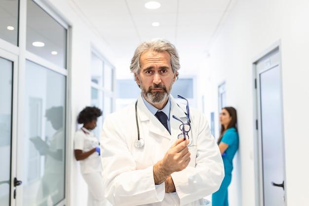 Médico posando com os braços cruzados no corredor do hospital, equipe médica em segundo plano.