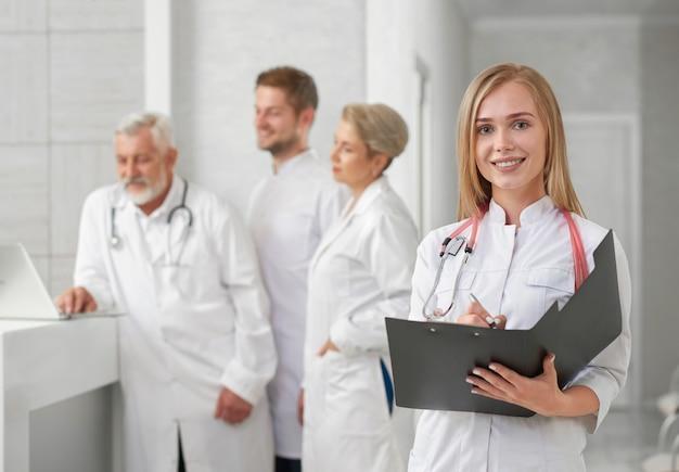 Médico posando, sorrindo, enquanto a equipe médica em pé atrás.