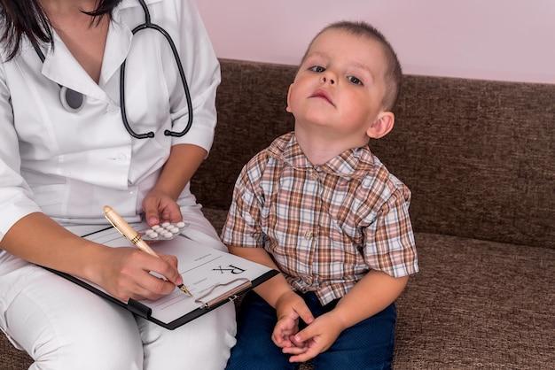 Médico preenchendo receita e menino sentado perto