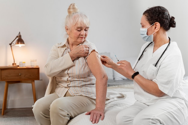 Médico preparando a vacina para uma mulher idosa