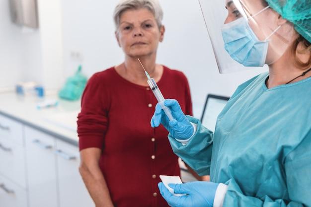 Médico preparando vacina de coronavírus para paciente sênior