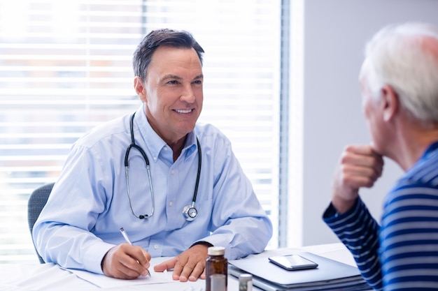 Médico prescrever medicamentos para paciente idoso