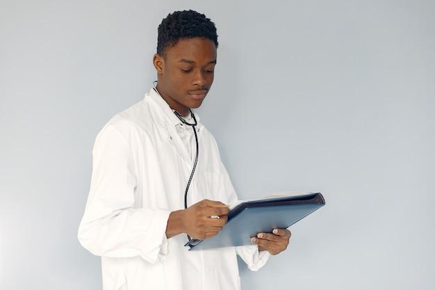 Médico preto em um uniforme branco com um estetoscópio