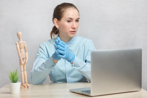 Médico professor lidera uma aula on-line através de uma vídeo chamada em um laptop.